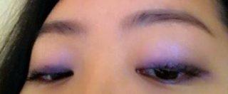 紫のアイシャドウを塗った女性
