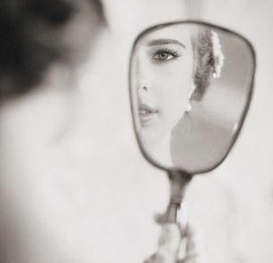 鏡で背中を見る女性