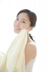 洗顔後タオルでふく女性