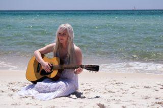 浜辺で優雅にギターを弾く美女