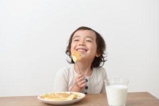 ホットケーキを笑顔で食べる子ども