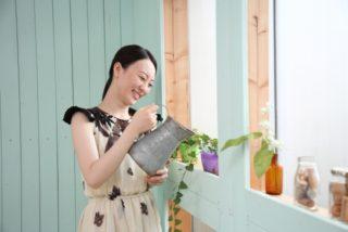 窓辺で植物に水をあげる女性
