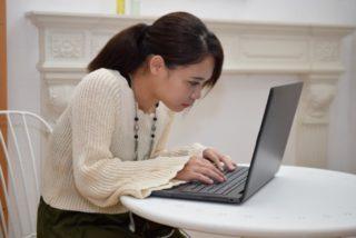 猫背でパソコンをしている女性